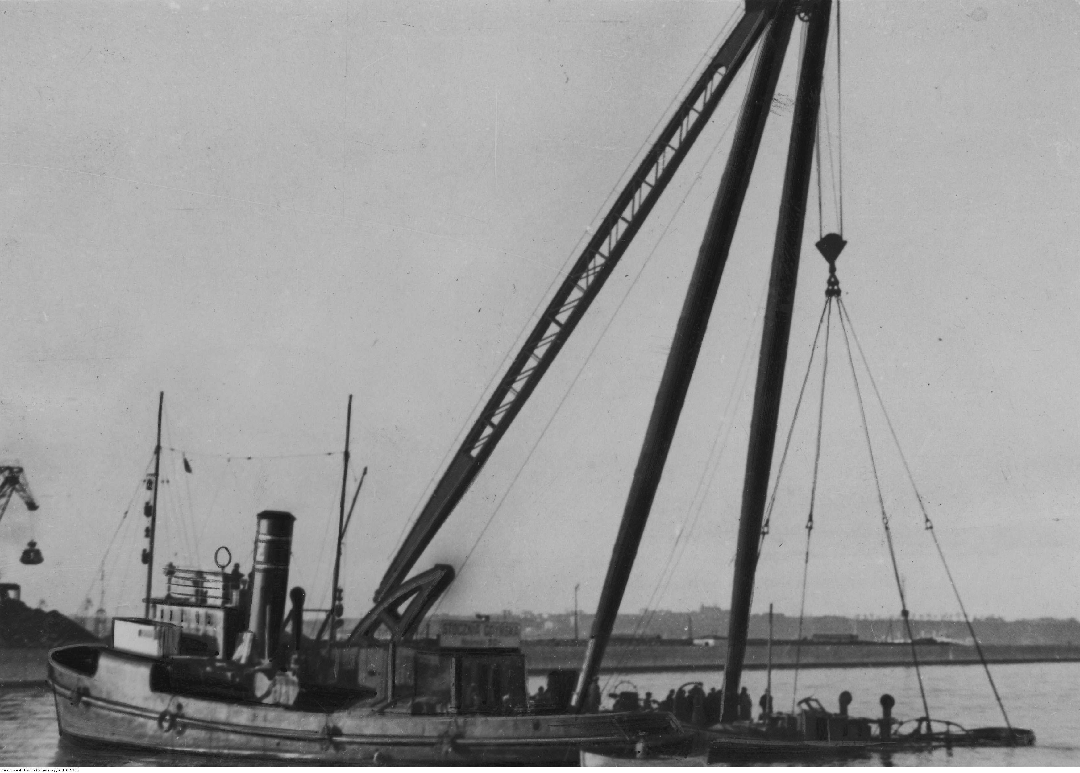 """Akcja wydobywania wraku holownika """"Żubr"""" przez holownik """"Ursus"""" oraz kran stoczni gdyńskiej."""