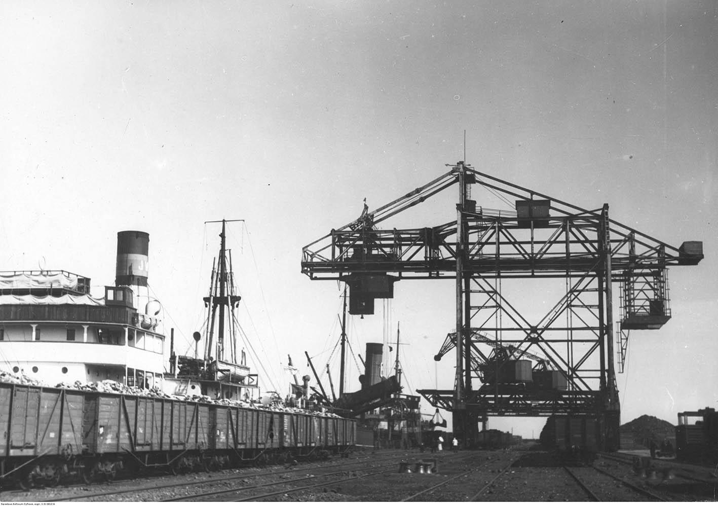 Dźwig portowy i wagony kolejowe na nabrzeżu szwedzkim.