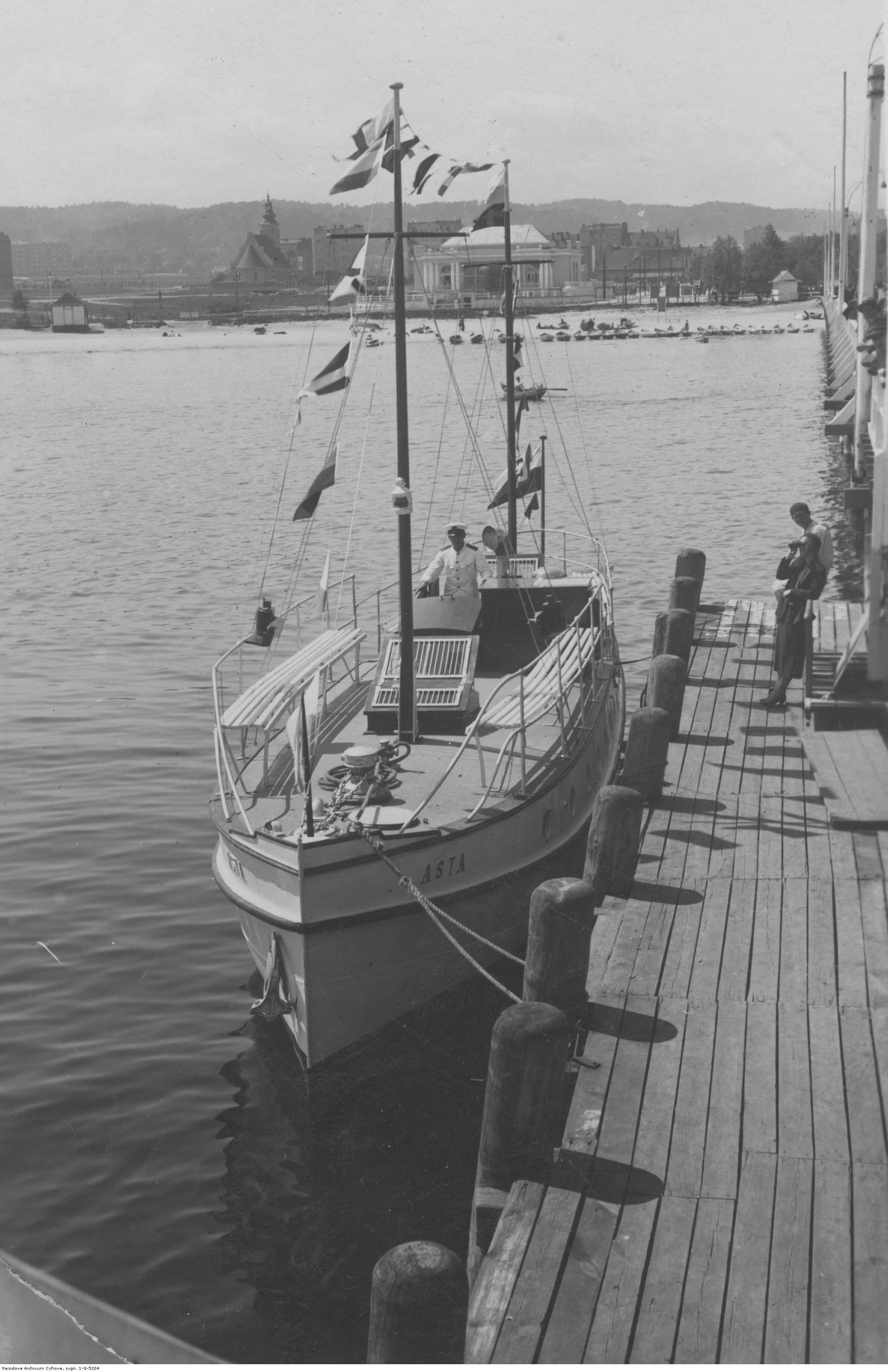"""Motorówka """"Asta"""" w gali flagowej podczas postoju przy drewnianym molo pasażerskim w Gdyni."""