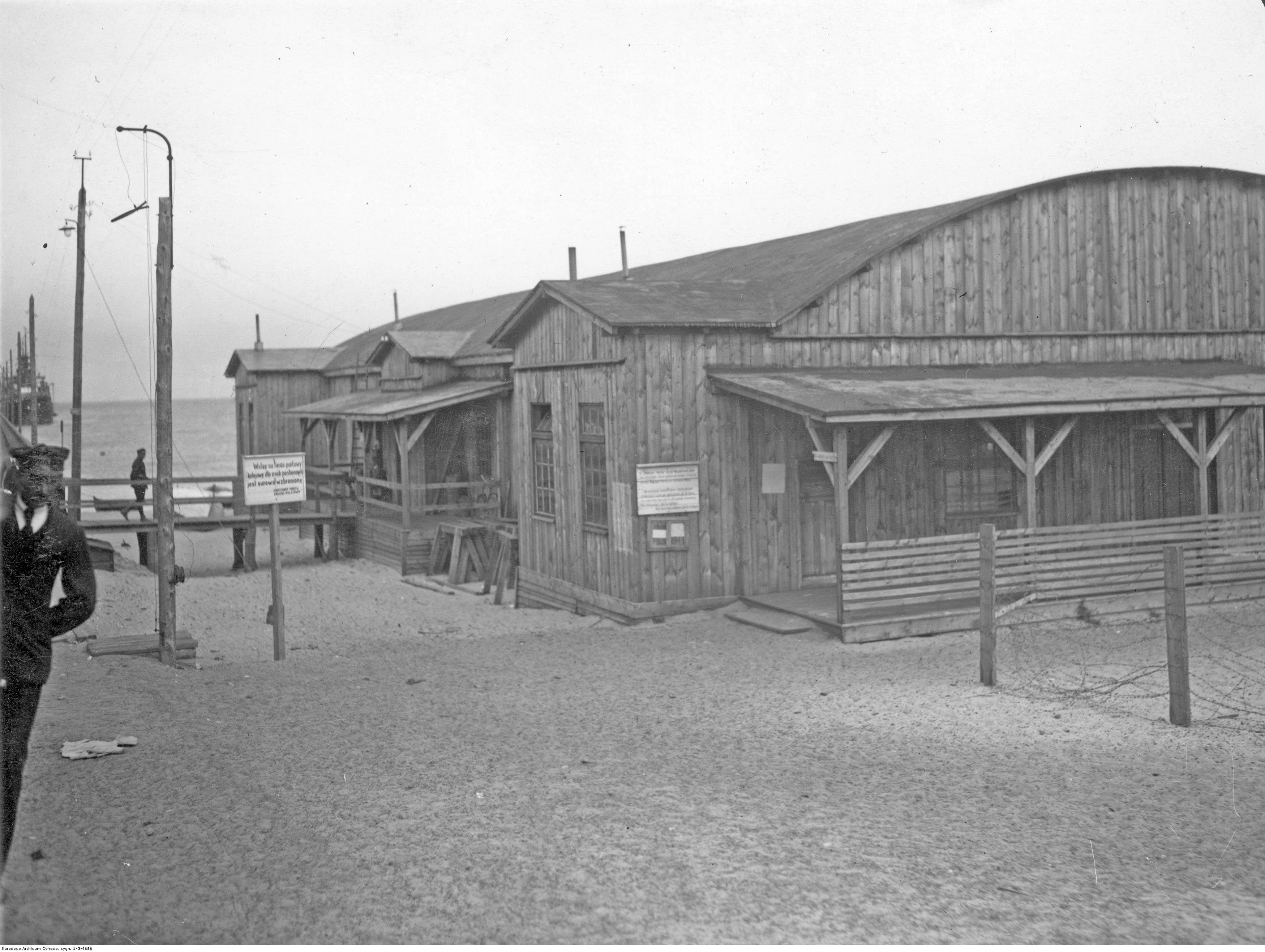 Drewniane budynki portowe przy prowizorycznym molo.