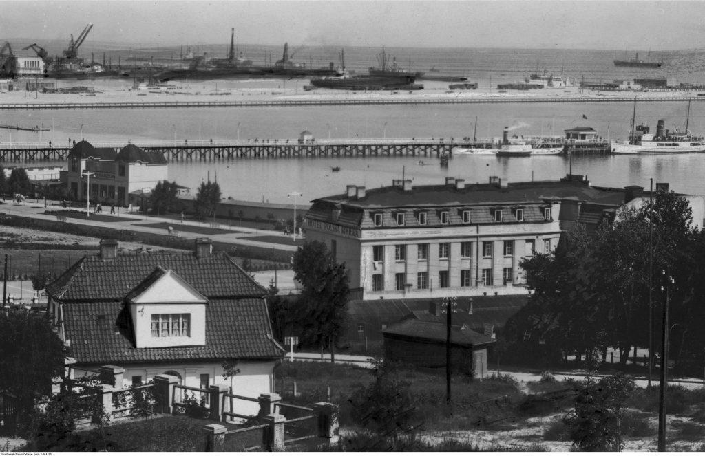 """Budynek hotelu Polska Riwiera i drewniane molo pasażerskie """"Żeglugi Polskiej""""."""