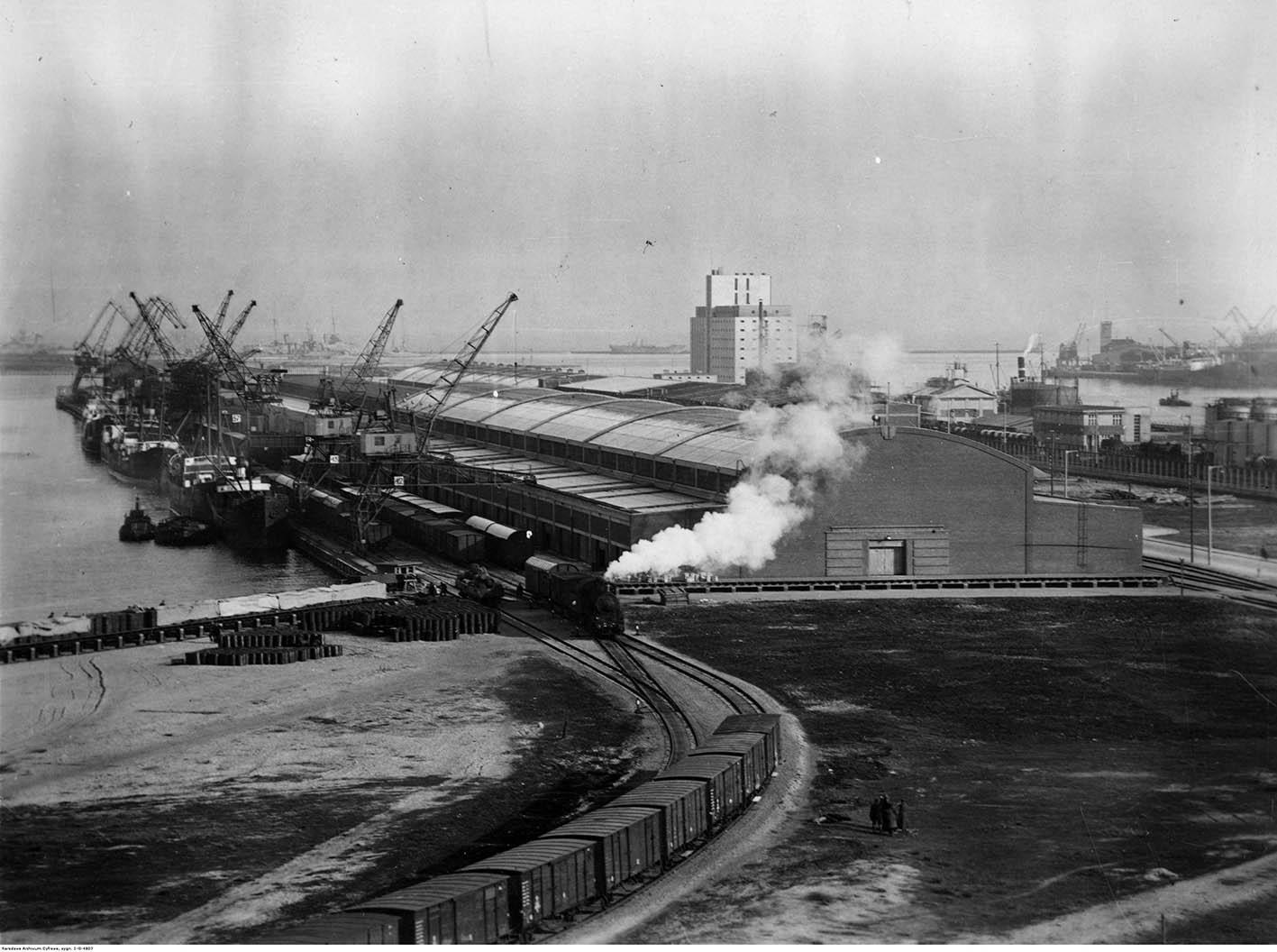 Pociągi towarowe, dźwigi portowe, budynki magazynowe, statki cumujące przy nabrzeżu Stanów Zjednoczonych w strefie wolnocłowej.