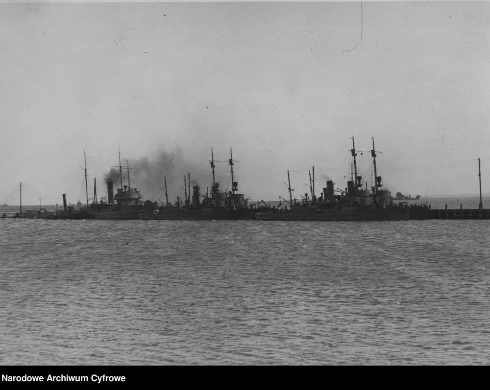 [ORP GENERAŁ HALLER] Okręty Marynarki Wojennej przy gdyńskim molo. Z prawej i pośrodku dwie pary trałowców typu FM, z lewej, z dymiącym kominem ORP GENERAŁ HALLER