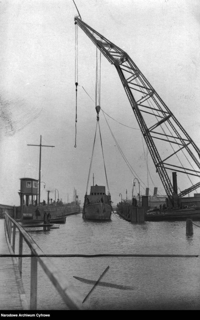 Wyłowiony trałowiec ORP MEWA wprowadzany do portu przy pomocy dźwigu. Widoczny m.in. żuraw pływający Długi Henryk